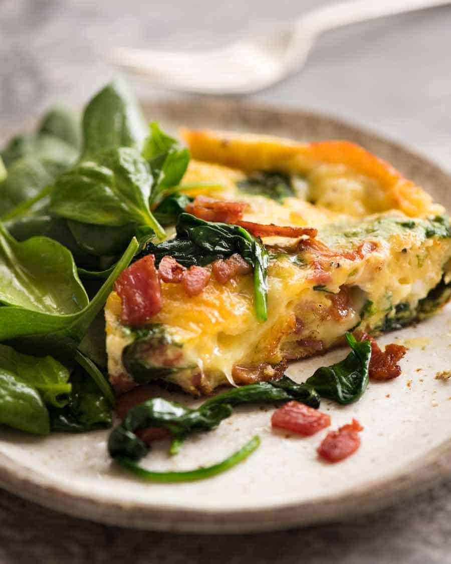 Slice of Frittata with Bacon and Spinach on a plate with a side of salad, ready to be eaten